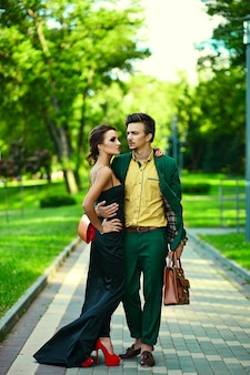 Portrait of sexy stylish woman in black dress and handsome man in modern evening business green costume in the street