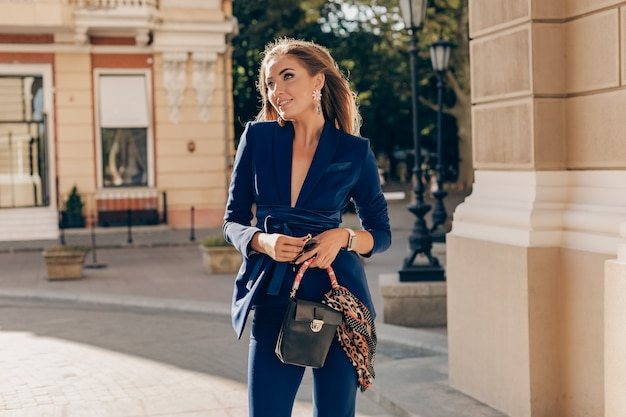 Portrait of sexy stylish woman walking in street in blue suit on sunny autumn day