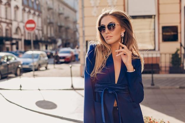 Ritratto di donna alla moda sexy che cammina in strada in vestito blu che indossa occhiali da sole in giornata di sole autunnale