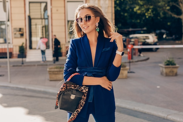 Portrait of sexy stylish woman walking in street in blue suit wearing sunglasses on sunny autumn day