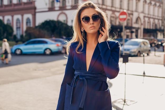 Ritratto di donna elegante sexy che cammina in strada in tuta blu indossando occhiali da sole il giorno di estate pieno di sole