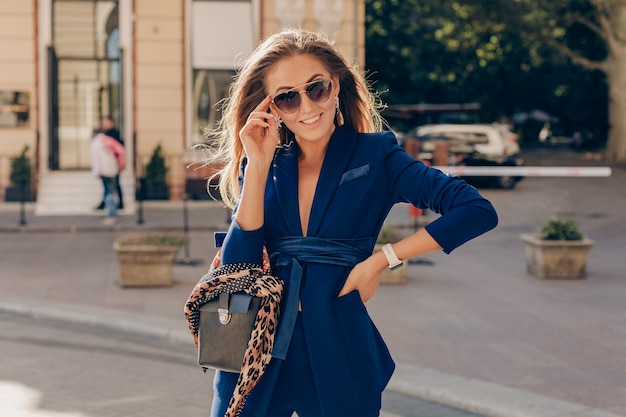 Portrait of sexy stylish woman walking in street in blue suit wearing sunglasses on sunny summer day