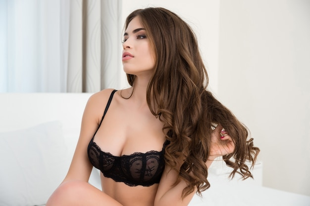 Portrait of a sexy woman in lingerie and long hair sitting on the bed
