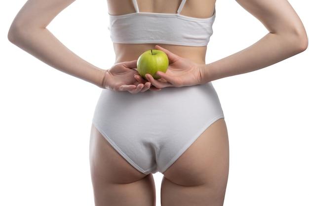 手に青リンゴ、健康的な食事療法の概念を持つランジェリーや下着を身に着けている肖像画のセクシーな女性。