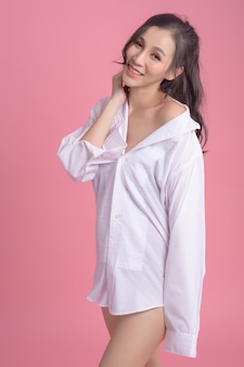 Portrait of sexy woman wearing a white shirt on pink
