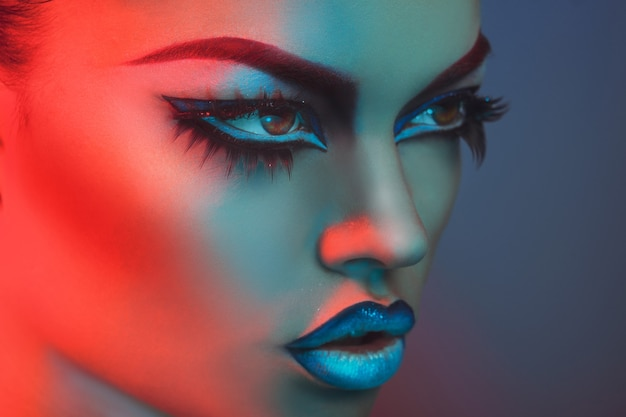 Portrait of sexy woman with healthy skin in red and blue lights in studio