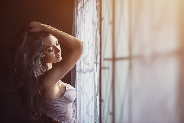 Portrait of sexy women in underwear near window. relaxing near window