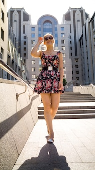 Portrait of sexy young woman in short dress posing against modern building made of concrete and glass in sun light rays