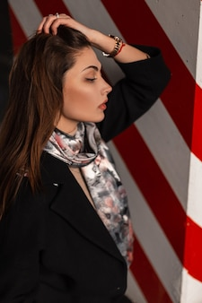 Portrait sexy young woman with beautiful lips with natural make-up in black stylish black coat with silk scarf with print flowers near red-white pillar. beautiful girl brunette relaxes outdoors.