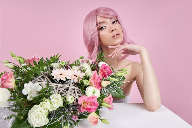 Portrait sexy young woman with pink hair, beautiful bouquet flowers in hand.