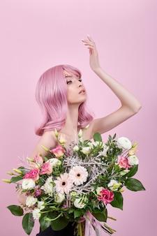 분홍색 머리를 가진 초상화 섹시 한 젊은 여자, 손에 아름 다운 꽃다발 꽃. 완벽한 헤어 스타일과 헤어 컬러링. 아름다운 눈과 긴 분홍색 머리를 가진 소녀