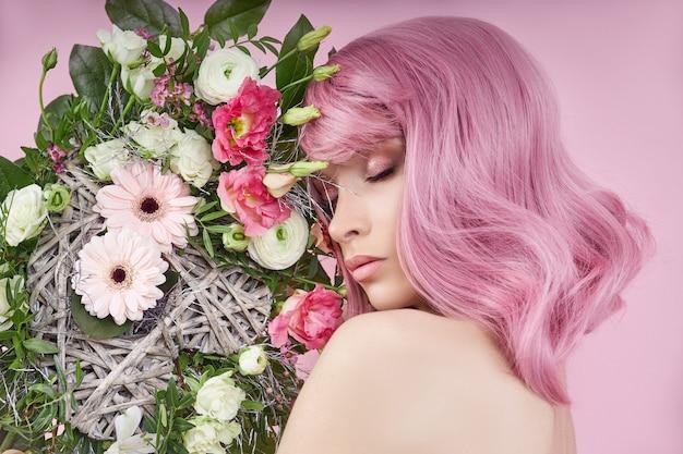 ピンクの髪、手に美しい花束の花を持つ肖像画のセクシーな若い女性。完璧なヘアスタイルとヘアカラー。美しい目と長いピンクの髪の少女