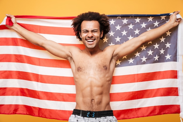 Portrait of a shirtless afro american man holding usa flag