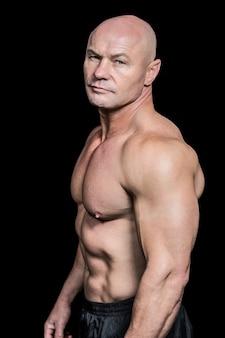Portrait of shirtless bald man standing against black background
