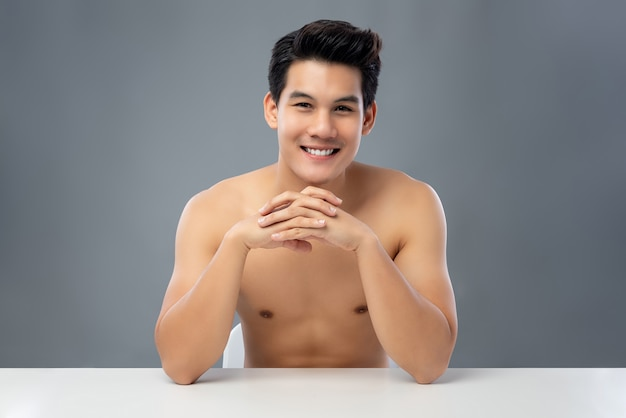 Portrait of shirtless handsome smiling young asian man sitting with hands clasp