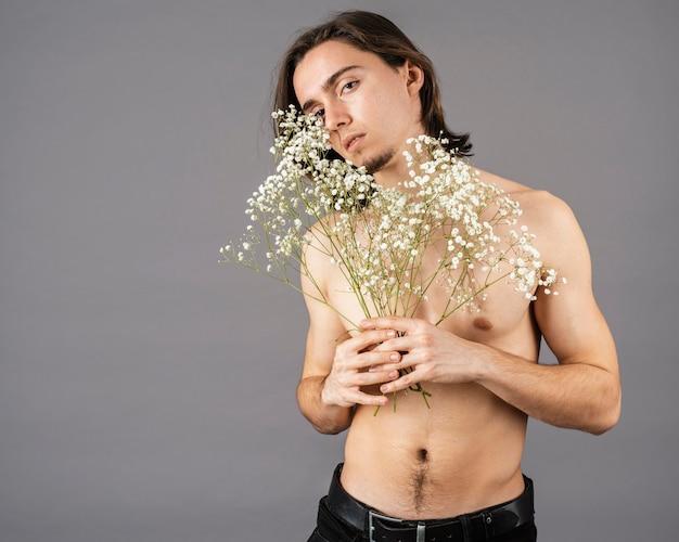 Ritratto dell'uomo senza camicia che tiene i fiori
