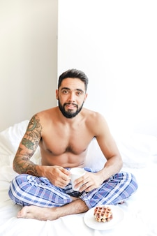 Portrait of a shirtless man sitting on bed with cup of coffee and waffle on plate