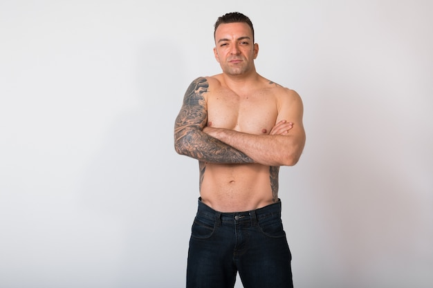 Portrait of shirtless man with tattoos against white wall