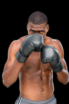 Portrait of a shirtless muscular boxer in defensive stance