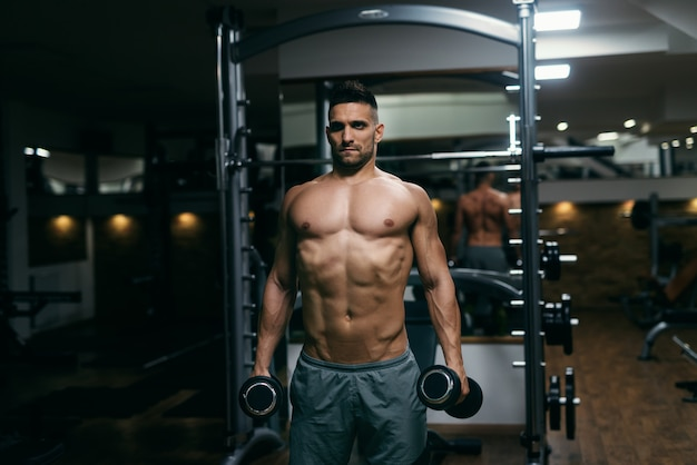 Portrait of shirtless muscular man standing and holding dumbbells in hands