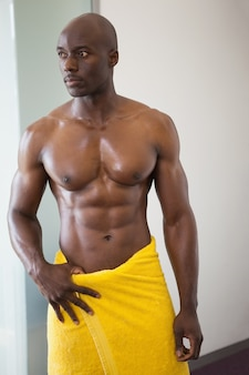 Portrait of a shirtless muscular man wrapped in yellow towel