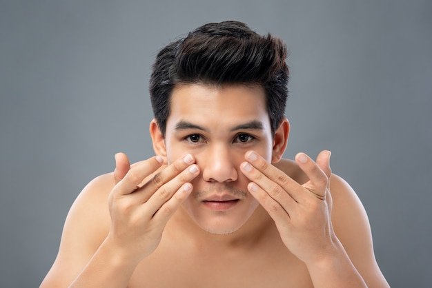 Portrait of shirtless young handsome asian man checking his face skin
