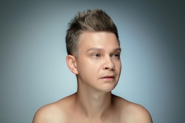 Ritratto di giovane senza camicia isolato sul muro grigio. modello maschio sano caucasico che esamina lato e posa. concetto di salute e bellezza maschile, cura di sé, cura del corpo e della pelle.