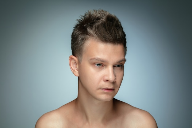 Portrait of shirtless young man isolated on grey  wall. caucasian healthy male model looking at side and posing. concept of men's health and beauty, self-care, body and skin care.