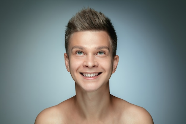 Ritratto di giovane senza camicia isolato sul muro grigio. modello maschio sano caucasico che osserva in su e che posa. concetto di salute e bellezza maschile, cura di sé, cura del corpo e della pelle.