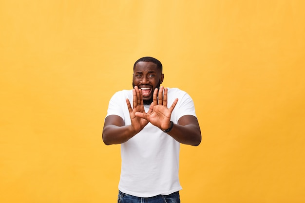 Portrait shock and annoyed displeased young man raising hands up to say no stop right there isolated orange background