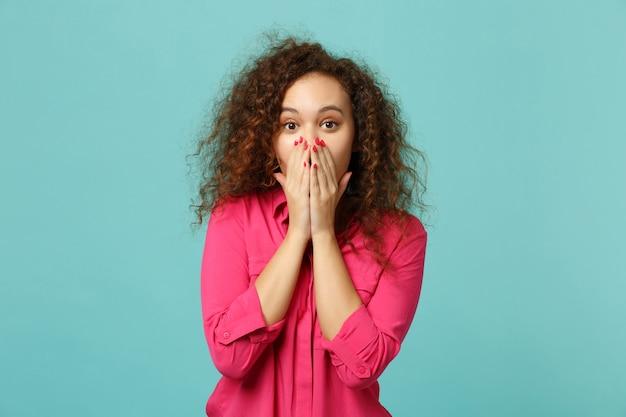 Ritratto di una ragazza africana scioccata in abiti casual rosa che copre la bocca con le mani isolate sul fondo della parete turchese blu in studio. persone sincere emozioni, concetto di stile di vita. mock up copia spazio.