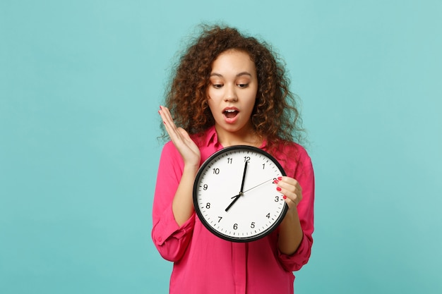 Portrait of shocked amazed african girl in pink casual clothes holding round clock isolated on blue turquoise wall background in studio. people sincere emotions, lifestyle concept. mock up copy space.