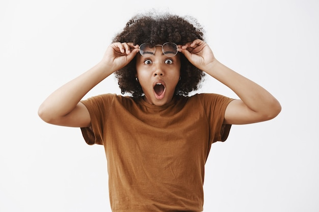 Portrait of shocked and amazed excited good-looking dark-skinned female with afro hairstyle taking off glasses and holding eyewear on forehead dropping jaw from excitement and thrill