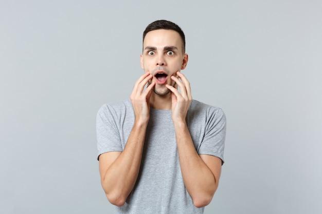 Ritratto di giovane stupito scioccato in abiti casual che tiene la bocca aperta, mettendo le mani sul viso on
