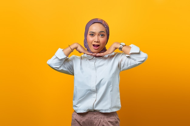 Portrait of shocked asian woman with open mouth over yellow background
