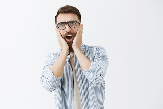 Ritratto di uomo barbuto scioccato e stupito in posa contro il muro bianco