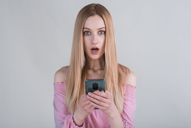 Portrait of a shocked blonde girl with a smartphone in the studio on a white background