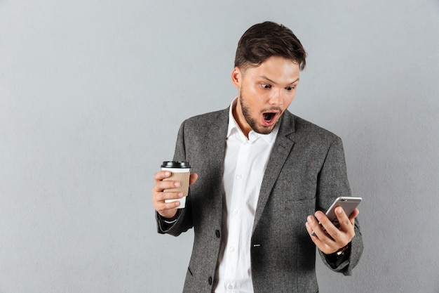 Portrait of a shocked businessman looking at mobile phone