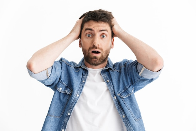 Portrait of a shocked confused handsome bearded man wearing casual clothes standing isolated