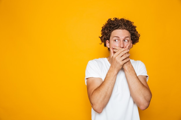 Portrait of a shocked curly haired man covering mouth
