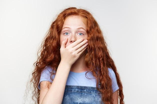 Ritratto di bambina lentigginosa carina scioccata con i capelli rossi, sente notizie incredibili, bocca coperta con la mano, si leva in piedi sopra il muro bianco con gli occhi spalancati con espressione sorpresa.