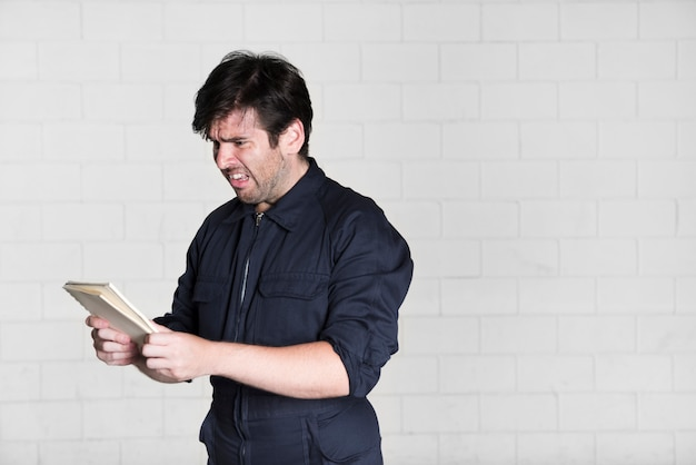 Portrait of shocked electrician looking at book