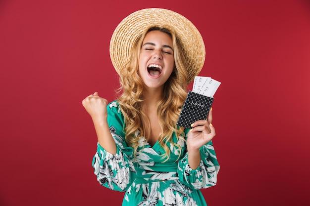 Portrait of shocked excited young blonde girl tourist in bright blue dress posing isolated over red wall holding passport with tickets makes winner gesture