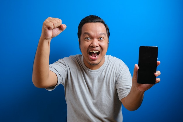 Portrait of shocked fat asian man in grey t-shirt pointing at cellphone and looking at camera with amazement. man shows winning gesture by raising his hand. studio shot isolated on blue background