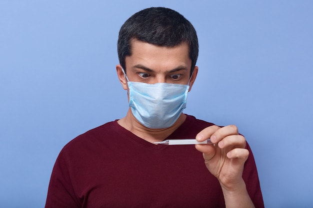 Portrait of shocked frightened young man holding thermometer in one hand, looking at temperature, having fever, being infected, wearing mask, having scared facial expression. coronavirus concept.