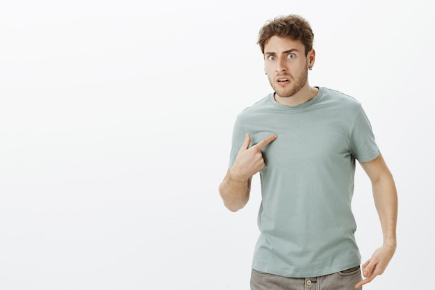 Portrait of shocked frustrated handsome european man in earrings, pointing at himself with index finger and frowning, asking question