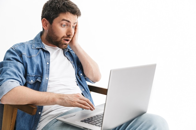 Portrait of a shocked handsome bearded man wearing casual clothes sitting in chair isolated over white wall, working on laptop computer