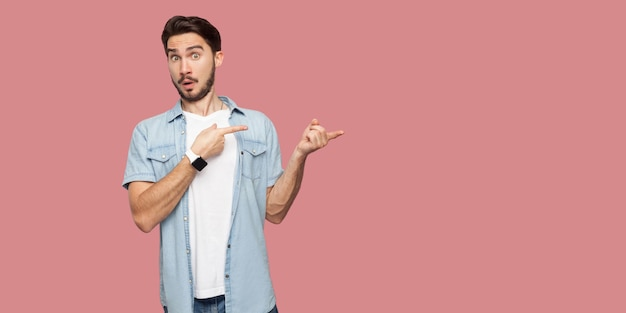 Portrait of shocked handsome bearded young man in blue casual shirt standing, looking at camera with surprised face and pointing at wall copyspace. indoor studio shot, isolated on pink background.