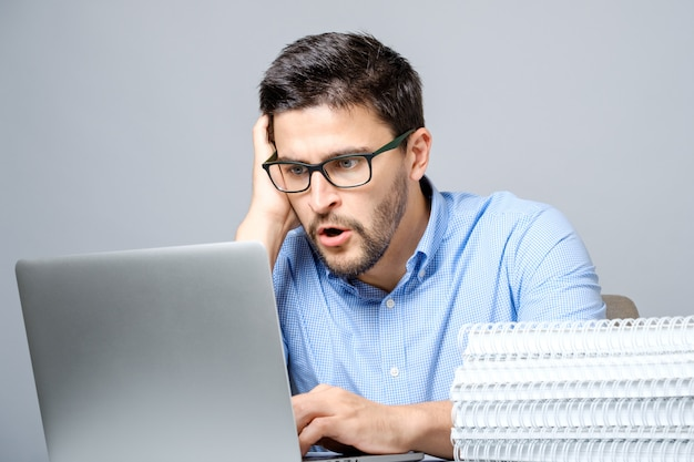 Portrait of shocked man sitting at the table with laptop