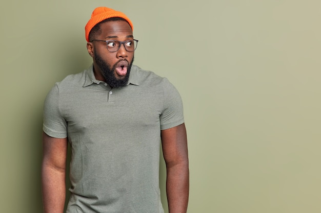 Portrait of shocked man stares with widely opened eyes and mouth reacts emotionally on amazing news wears orange hat csual t shirt and spectacles isolated over green wall